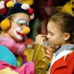 Clown putting make-up on a girl